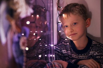 Calm little boy on the windoe with Christmas Lights