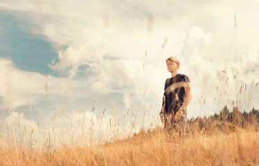 Young man enjoy with tender breeze on golden field