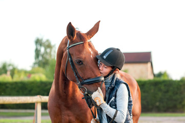 Young teenage girl equestrian kissing her chestnut horse.