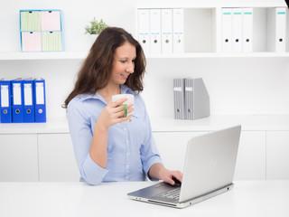 junge frau trinkt entspannt einen kaffee am pc