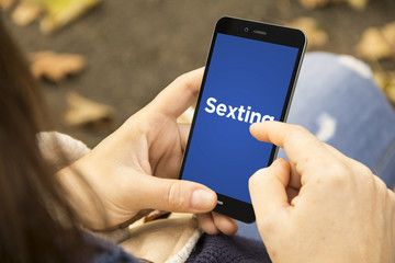 woman with sexting phone in the park