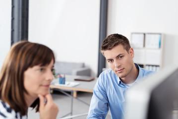 zwei kollegen schauen konzentriert auf den computer-bildschirm