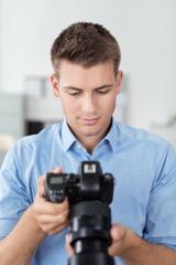 mann im fotostudio schaut auf seine digitalkamera