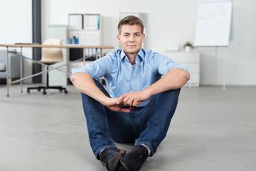 sympathischer geschäftsmann sitzt auf dem fußboden im büro