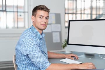 junger geschäftsmann arbeitet am pc im büro
