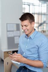 mann im büro schreibt eine nachricht auf seinem smartphone