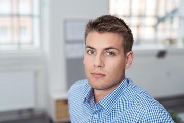 entschlossenener junger mann im büro schaut in die kamera