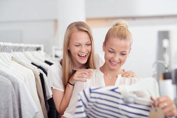 zwei lachende freundinnen auf shopping-tour