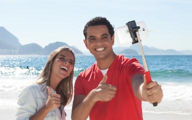 Liebespaar im Urlaub macht Selfie am Strand