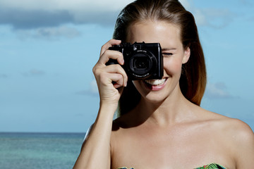 beautiful smiling woman taking photos on the beach