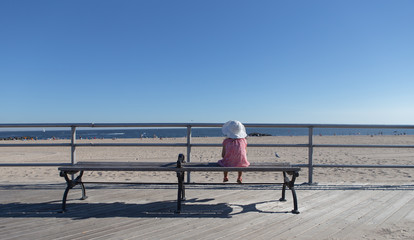 Little girl sitting on the bench looking out at the ocean