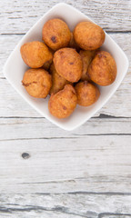Popular Malaysian fritter snack deep fried banana balls or locally known as Cekodok Pisang in white bowl