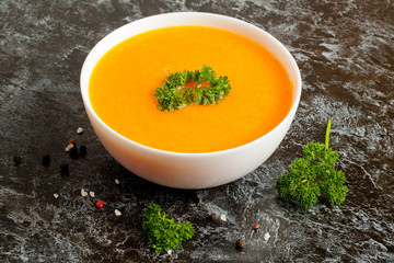 carrot soup with parsley on  table, horizontal