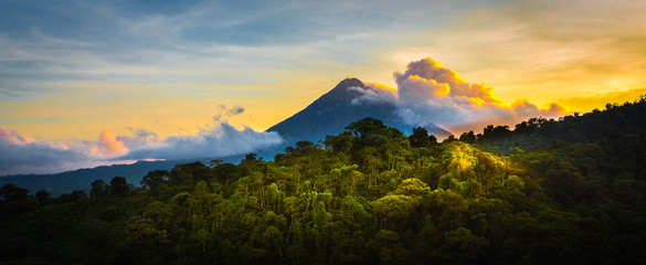 Photo sur Plexiglas Jungle Arenal Volcano at Sunrise...A rare sight at the perfect 15 second window to capture sunrise in all of it's glory. Light glistens off the clouds and the mountain and the jungle.