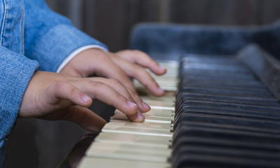 Child playing piano with selective focus and shallow depth of