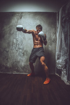 Shirtless muscular fighter in action.