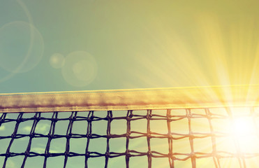 Tennis net with sunset sky in the background