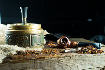 Ashtray and pipe on a wooden table