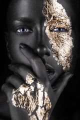 Tuinposter Bestsellers fashion portrait of a dark-skinned girl with gold make-up