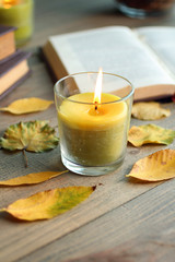 candle with leaves and books on wooden background