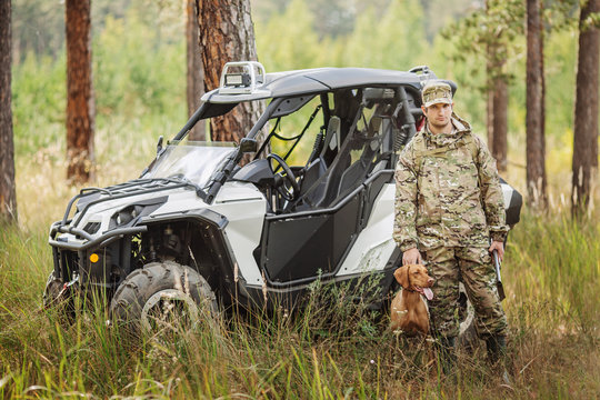 Hunter with Rifle and Four Wheeler Tire in forest