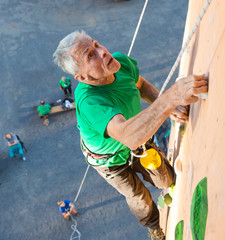 Aged Person Practicing Extreme Sport Elderly Male Climber Makes Hard Move and Looking High Up on Outdoor Climbing Wall Sport Competitions Very Emotional Face Belaying Partner Staying on Remote Ground