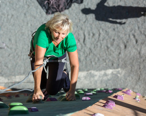 Aged Lady Doing Extreme Sport Elderly Female Makes Hard Move on Outdoor Climbing Wall Sporty Clothing on Fitness Training Shadow of Her Belaying Partner on Background