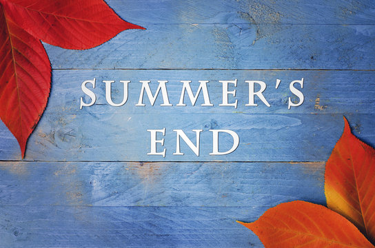 the text summer's end written on wooden, blue background with autumn's leaves in corners