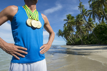 First place Brazilian athlete standing with gold medals on empty beach