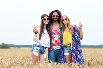 happy young hippie friends showing peace outdoors
