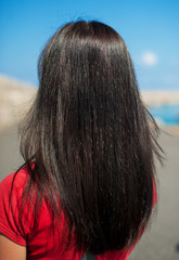 view of a young woman with long dark brown straight hair on the