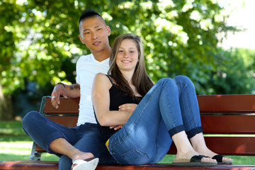 Young mixed couple sitting on a bench in a park