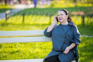Mature woman using smartphone sitting on a bench in the park. Smiling and talking on the phone