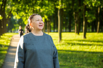 Mature woman walking in the sunny park. Smiling and looking around