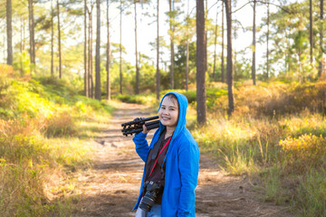 Thai asian woman traveler take a photo and enjoying in Phu Kradueng National Park at sunset time in Loei Province, Thailand