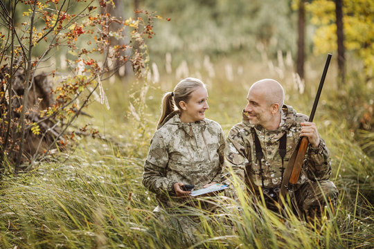 Hunters with Rifle and Four Wheeler Tire in forest