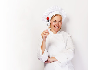 Woman chef showing a sign perfect, with tomato on fork, over whi