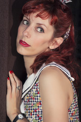 View of pinup young woman in vintage style clothing over a rusty iron wall.