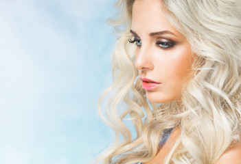 Beautiful woman - blonde, close-up on a blue background, looked down