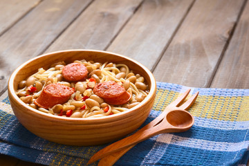 Traditional Chilean dish Porotos con Riendas, made of cooked beans, linguine, fried sausage, photographed with natural light (Selective Focus, Focus one third into dish)