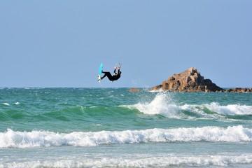 Un kitesurfeur dans les airs au dessus des vagues sur la plage de Trestel en Bretagne
