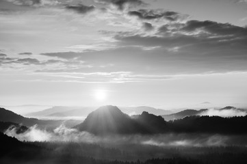 Autumn sunrise panorama  in a beautiful mountain within inversion. Peaks of hills increased from heavy  fogg