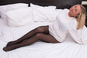 sexy beautiful woman in black pantyhose on the bed