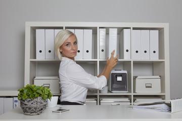 Sekretärin nimmt eine Akte aus dem Aktenschrank