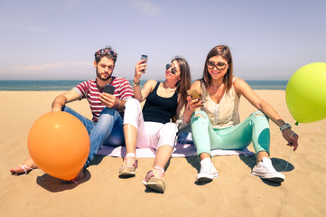 Group of happy young friends having fun with mobile phone on the beach - 3 students taking selfie internet chatting with modern smartphone - Friendship and new technologys concept in a summer vacation