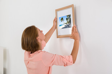 Woman Putting Photo Frame On Wall
