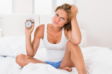 Woman Sitting On Bed With Alarm Clock