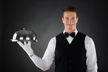 Waiter Holding Cloche Over Tray