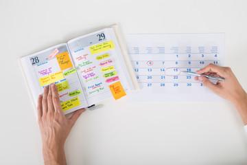 Fototapete - Person Hands Highlighting Date On Calendar