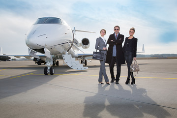 business team standing in front of private jet